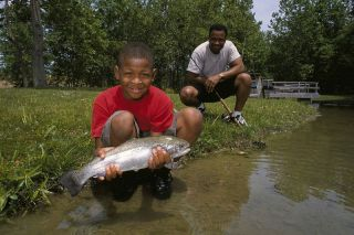 A_father_and_son_get_their_picture_taken_with_fish_in_hand - Copy