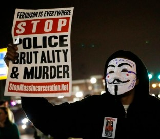 A protestor wearing a Guy Fawkes mask holds a sign as demonstrators march through the streets of Ferguson, Missouri